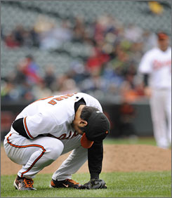 Orioles pitcher Koji Uehara leans over and clutches his chest after getting hit with a line drive off the bat of the Angels' Gary Matthews in the seventh inning.