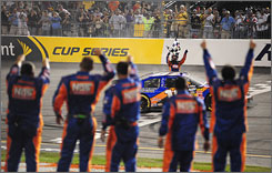 Kyle Busch waves the checkered flag at the start-finish line as his crew celebrates his Nationwide victory on pit road at Richmond.