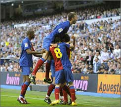 Barcelona players celebrate one of their many goals in front of a stunned Real Madrid crowd.