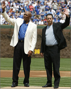 Former Chicago Cubs' Ferguson Jenkins, left, and Greg Maddux wave to fans as they celebrate at Wrigley Field as the Cubs retire the No. 31, which both wore with the team.