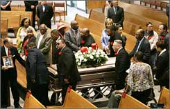 Pallbearers bring the casket of former heavyweight boxing champion Greg Page into Our Lady of Mt. Carmel Church for his funeral. Boxing gloves are in the middle of the floral arrangements.