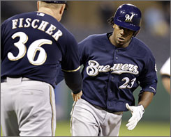 The Brewers' Rickie Weeks rounds third and is congratulated by coach Brad Fischer after hitting a thee-run home run off Pirates closer Matt Capps in the ninth inning.