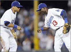 Dodgers first baseman James Loney, left, and second baseman Orlando Hudson celebrate after beating the Arizona Diamondbacks 3-1 on Tuesday to tie the modern baseball record with 11 consecutive home victories to open a season.