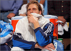 Dallas' Dirk Nowitzki watches the closing minutes of the Mavs' Game 2 loss to the Nuggets.