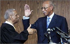 Dave Bing raises his right hand as he takes the oath of office for Detroit mayor from U.S. Court of Appeals Judge Damon Keith.