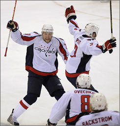 David Steckel, left, celebrates after scoring off a deflection in overtime, helping the Capitals force a series-deciding Game 7 against the Penguins back in Washington.