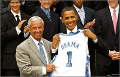 North Carolina head coach Roy Williams presents President Obama with a Tar Heels jersey during a ceremony toasting the NCAA men's basketball champions at the White House in Washington.