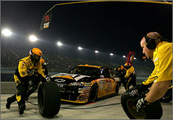 Jeff Burton's crew hustles around his Chevy during a pit stop earlier this season at California.