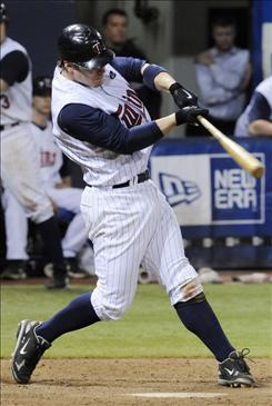 Minnesota Twins third baseman Joe Crede hits a grand slam off Detroit Tigers reliever Brandon Lyon in the 13th inning Wednesday night in Minneapolis, where the Twins beat the Tigers 14-10.