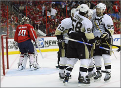 The Penguins' Kris Letang, Sergei Gonchar (55) and Bill Guerin (13) celebrate teammate Sidney Crosby's first-period goal near Capitals goalie Simeon Varlamov. Pittsburgh chased Varlamov after taking a 4-0 lead in the second period.