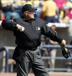 In this photograph taken on Monday, May 11, 2009, home plate umpire Rick Reed tosses a ball to the pitcher during the Toledo Mud Hens minor league baseball game against the Lehigh Valley IronPigs at Fifth/Third Field in Toledo, Ohio. Reed stepped behind the plate for the first time since suffering two strokes that kept him off the field since last May. He's rehabbing in the minors and plans to return to the majors May 21 in Chicago.