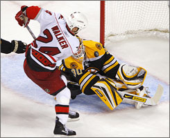 The Hurricanes' Scott Walker, flips the puck over the shoulder of Bruins goalie Tim Thomas and into the net for the game-winning goal in overtime, sending Carolina to the Eastern Conference finals.
