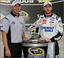Jimmie Johnson, right, poses alongside crew chief Chad Knaus and their team's trophy for winning the All-Star race pole.