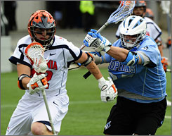 Johns Hopkins' Tim Donovan pursues Virginia's Max Pomper during a 19-8 loss, the worst playoff defeat in team history.