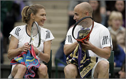 Spouses and former tennis champions Steffi Graf and Andre Agassi take a break during a mixed doubles exhibition against Kim Clijsters and Tim Henman during a test event on Wimbledon's Centre Court.