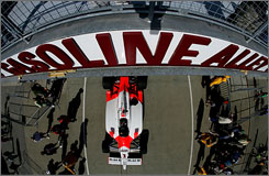 Helio Castroneves' Team Penske Dallara Honda passes through Gasoline Alley during a recent practice. The old wooden garages were replaced in 1986.