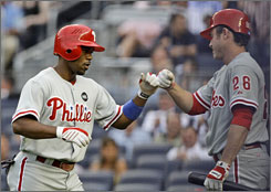 The Phillies' Jimmy Rollins, left, celebrates with teammate Chase Utley after hitting a home run in the first inning against the Yankees.