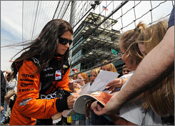 Danica Patrick signs autographs for fans during practice at Indianapolis Motor Speedway.