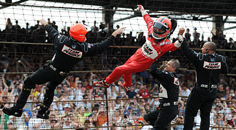"Helio Castroneves does his trademark ""Spiderman"" victory celebration by climbing the frontstretch fence with members of his crew."