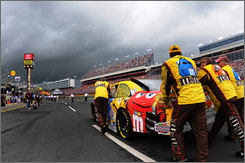 Kyle Busch's crew pushes his car back to the garage as storm clouds loom over Lowe's Motor Speedway.