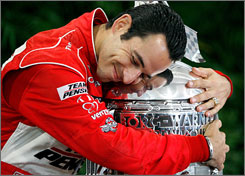 Helio Castroneves embraces the Borg-Warner Trophy a day after securing his third Indy 500 crown.