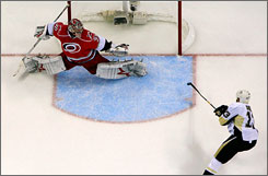 Bill Guerin shoots the puck past         Cam Ward for the Penguins' third goal of the game.