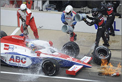 Vitor Meira's car is doused with water after a refueling incident triggered a midrace fire. Meira's A.J. Foyt team got a helping hand from Will Power's Team Penske crew in putting out the flames.