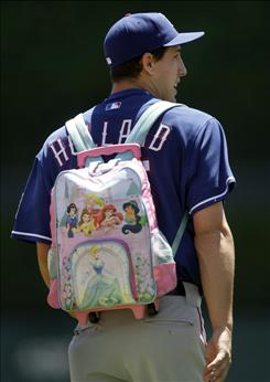 Texas Rangers relief pitcher Derek Holland, 22, wears a child's backpack to the bullpen prior to a game against the Detroit Tigers in May.