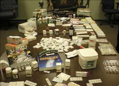 Anabolic steroid pills, injectable liquids and syringes confiscated from the home of Richard and Sandra Thomas in Lakeland, Fla., are shown at the Polk County Sheriff's office in Bartow, Fla. The Thomases were charged Tuesday with several counts of possession of illegal steroids, firearms and maintaining a dwelling for drug use.