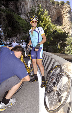 Lance Armstrong waits on the side of the road for a wheel change after a minor fall during Stage 19 of the Giro d'Italia on Friday.