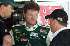 Dale Earnhardt Jr. talks things over with interim crew chief Brian Whitesell, right, and another crewman during practice at Dover International Speedway.