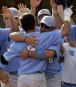 North Carolina's Mike McKee hugs Garrett Gore (4) after the latter homered against Kansas during an NCAA regional final in Chapel Hill, N.C. Gore knocked in five RBI in the 12-1 Tar Heels victory. North Carolina has not finished below third place in the past three College World Series.