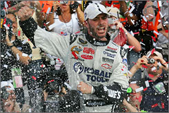 Drinking it in: Jimmie Johnson celebrates amid a shower of confetti in victory lane after winning Sunday's 400-miler at Dover.