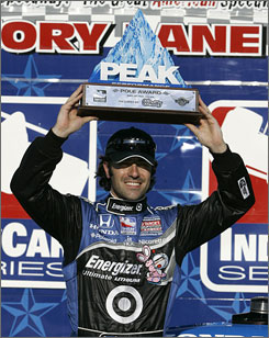 Dario Franchitti lifts the trophy after winning the pole for Saturday's IndyCar Series Bombardier Learjet 550 at Texas Motor Speedway.