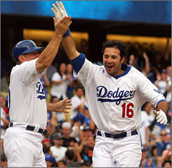Third base coach Larry Bowa high-fives Andre Ethier after Ethier connected on his game-winning solo home run in the bottom of the 12th inning against the Phillies on Saturday.