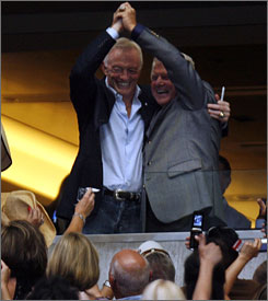 Cowboys owner Jerry Jones, left, and former Cowboys coach and current NFL analyst Jimmy Johnson pose for fans from a suite at a country music concert that was the first event held at the new Cowboys Stadium.