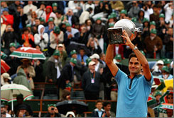 Roger Federer hoists the championship trophy after his victory over Robin Soderling at the French Open on Sunday. With the win, Federer completes a career Grand Slam and tied Pete Sampras' record for the most all-time Grand Slam victories among men.
