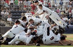 Virginia players pile on each other after securing their first College World Series birth ever following a 5-1 win over Mississippi on Sunday. The Cavaliers won their NCAA super regional baseball championship game in Oxford, Miss. and will head to Omaha next weekend.