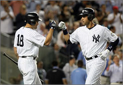 The Yankees' Johnny Damon, left, congratulates teammate Derek Jeter after Jeter hit a solo home run in the eighth inning.