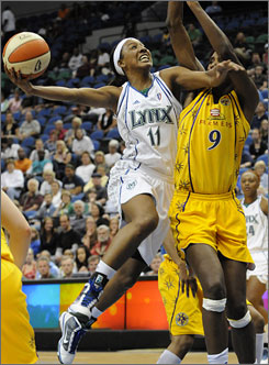 Minnesota's Candice Wiggins, left, putting up a shot as the Sparks' Lisa Leslie defends, scored 17 points to help the Lynx improve to 3-0.