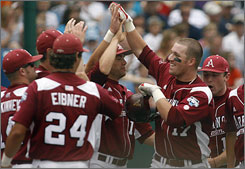 Arkansas first baseman Andy Wilkins, right, is swarmed by teammates after belting a fourth-inning home run.
