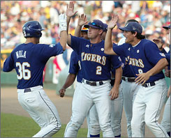 Austin Nola, right, is congratulated by teammates after his home run in LSU's victory over Arkansas at the College World Series. Since Nola entered the starting lineup at shortstop -- which moved numerous other players around the diamond -- the Tigers are 25-4 and are undefeated so far in the NCAA tournament.