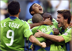 Seattle Sounders players celebrate a goal by Osvaldo Alonso, center, during the first half of their match against D.C. United. The teams played to a 3-3 tie.