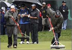 Tiger Woods and caddie Steve Williams wait on the second green as members of the grounds crew roll water off the green during first-round action at the U.S. Open.