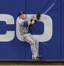 Atlanta Braves center fielder Nate McLouth crashes into the wall to make a catch off Cincinnati Reds' Jay Bruce for an out in the first inning June 16.