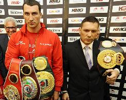 Vladimir Klitschko, left, and Ruslan Chagaev pose with an assortment of title belts Monday.