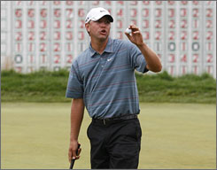 Lucas Glover will open Monday's play at the U.S. Open with a share of the lead with     Ricky Barnes.