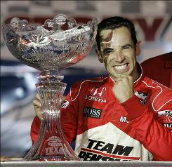 Helio Castroneves, shown here celebrating with the IndyCar Series Bombardier Learjet 550 auto race trophy following his win at Texas Motor Speedway, is seeking his first IRL IndyCar Series title this year.