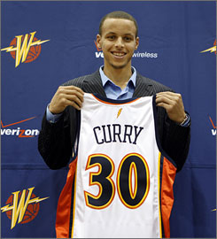Stephen Curry poses with a Golden State jersey after the Warriors selected the guard with the seventh overall pick in Thursday's NBA draft.