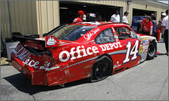 Tony Stewart's battered No. 14 Chevy pulls into the garage area at New Hampshire Motor Speedway.